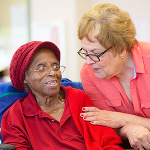 Hispanic and  African American women together in a busy senior center